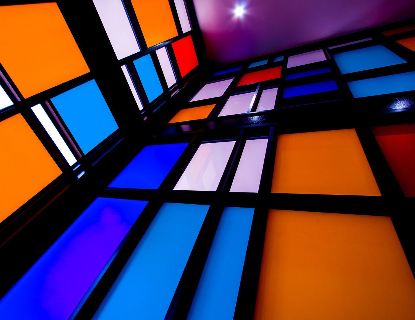 Mondrian-style glass walls in blues & orange in black frames via Pixabay